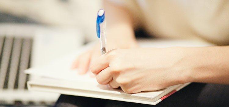 Frau schreibt mit Links auf Papier