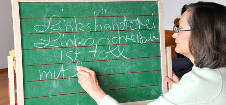 Marianne Dräger schreibt mit Links an einer Tafel